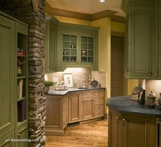 Cream and sage green cabinets...stone work in kitchen
