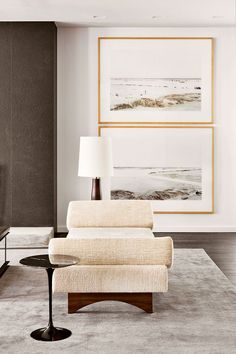 Simple seating area with a pair of large photography prints with natural wood frames and white matting. A very simple, understated space.