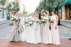 Bridesmaids and Bride take a group photo downtown on King St in Charleston SC.  Coordination | Mac & B Events >> Photography | Aaron and Jillian Photography >> Florist | Tiger Lily Florist