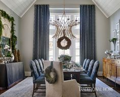 A blue-and-ivory rug sets the tone in the dining room where draperies in a fretwork-pattern fabric accent the bay windows. - Photo: Emily Jenkins Followill / Design: Amy Morris