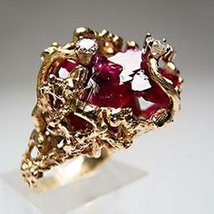 Raw ruby depths, four bright diamonds, and a gold nugget look. This takes my breath away.