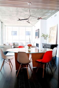 Modern dining space with mismatched chairs and bright natural lighting through windows