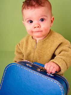 Toddler holding blue suitcase; Creative Tips for Traveling with Baby via @Parents Magazine