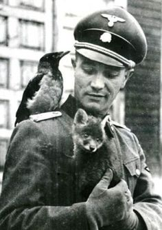 Waffen SS officer with two friends, one 4-legged, the other 2-legged but with wings. Even in the middle of the most brutal war, there are moments of kindness.
