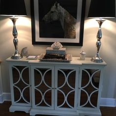 Stow fine china and tablecloths in the dining room or add extra storage space to the entryway with this classic cabinet, featuring a cream finish and elegant silver-hued cabinets.