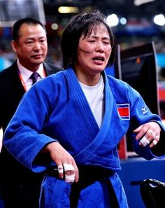 Kum Ae An of North Korea followed by her coach is unable to hold back her tears after winning the 52kgs gold medal.