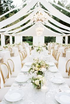 Almost all white wedding decor at this modern wedding at meadowood in Napa Valley from a savvy event and britt chudleigh. Spectacular draping, chandeliers, white floral centerpieces and gorgeous linens from la tavola linen.