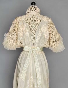 """Both embroidered cotton lawn, short sleeves & slightly longer underskirt: 1 w/ machine needlelace inserts, filet lace & narrow tulle ruffles, B 34"""", W 23.5"""", L 53"""", (brown stains on shoulders & skirt, sash in photo not included) very good; 1 w/ eyelet &ecru lace trim on bodice, scalloped tulle under skirt, B 32"""", W 22"""", L 50"""", (scattered small brown stains on bodice, 2 on skirt) very good."""