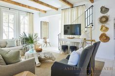 ASHLEY GILBREATH INTERIOR DESIGN: Natural elements and neutral tones give this Rosemary Beach living room cool vibes. Sheer drapery provides a backdrop for a suspended tv, and straw hats hung on pegs act as art. A large driftwood coffee table doubles as a conversation piece.