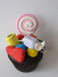 Candy Cupcake!  Who doesn't love candy! Cupcake topped with candy decorations including a lollipop, a wrapped hard candy, gumballs, all sorts, and a big foot all handcrafted in fondant.