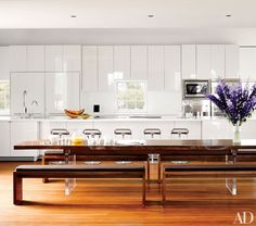 A kitchen featuring walnut-top table with acrylic supports and four walnut benches | archdigest.com