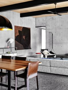 Open dining space with concrete walls, a wood dining table, and a large black pendant light