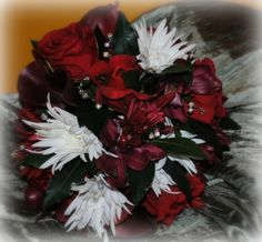 Beautiful red roses, wine colored orchids, white spider mums spiked with bling!