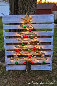 Christmas tree made by putting nails on a pallet that's been whitewashed then stringing lights and ornaments along it.