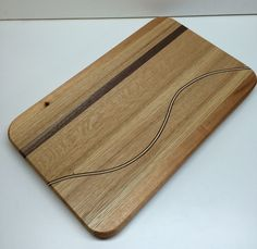 White oak and mahogany edge grain cutting board with a black walnut curved inlay and rubber feet. by HartmanWoodworks on Etsy