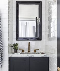 Gorgeous black and white contemporary bathroom boasts a Restoration Hardware Pharmacy Wall-Mount Medicine Cabinet framed by all white subway tiles accented with white grout.