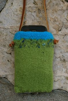 """This phone case is hand-knit and felted from 100% wool yarn. The result is a super sturdy and fun protective pouch. The dimensions are 5 1/2"""" x 3 1/2"""". It fits an iphone/ipod or most other cell phones. It has a 52"""" inch 1/4"""" wide leather shoulder strap. Colors are apple green and turquoise with a novelty yarn accent."""