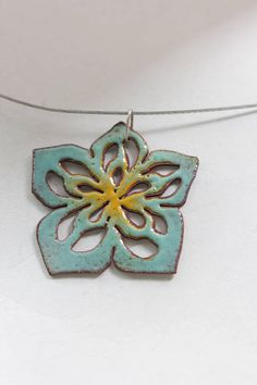 This pendant has been hand sawn from copper sheet using a jewelers saw, which was also used to cut out the pierced shapes. I then applied sifted glass enamels and used my jewelers torch to permanently fuse the colored glass to the pieces. The flower measures about 1 3/4 inches across, and is two color toned in aqua green and yellow. The backside is also enameled. Using the drop down menu, choose between a sterling silver chain or a nylon coated steel flex wire, and your preferred length....