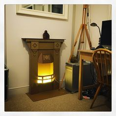 Cardboard fireplace with fairy lights.   by Finger in the Pie