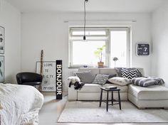 white modular lounge. lots of cushions. easy black stool.