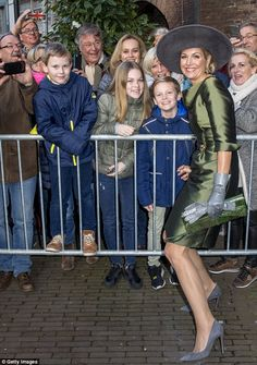 At 5ft 8in Maxima had to crouch down in order to pose for a photograph with children await...