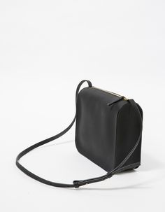 From Cuero&Mør, a minimalist smooth leather crossbady in Black. Features top zipper, leather pull tab, gold hardware, adjustable shoulder strap, unlined, standing structure and front gold pressed logo. • Smooth leather bag in Black • Two-way wrap-aro