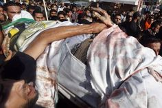 A Palestinian holds the hand of Ahmed Al-Jaabari, Hamas's military mastermind, during his funeral in Gaza City, November 15, 2012. Israel on Wednesday assassinated Al-Jaabari and shelled the enclave from the land, sea and air, killing 13 people, including five militants, three children and a pregnant woman. — Reuters Gaza Strip, Shelled, Three Kids, Funeral, Israel, Wednesday, November, Military, Sea