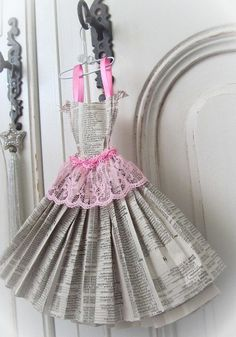This adorable dress miniature is made from phone book pages. It is carefully stitched in pink cotton. The petite dress has ribbon straps, lace trims