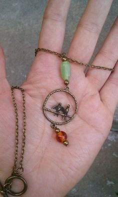 Long antique brass love bird pendant necklace with green and amber beads by johnnynjenny on Etsy