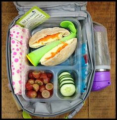 Since I am out of town this is the lunch my husband sent the kids off with today (after getting lots of detailed instructions  ) ... Whole-wheat pitas filled with hummus, cheese and carrot shreds, a frozen berry/banana/spinach/PB smoothie pop, grapes, cucumbers, and water.