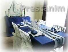 Ci contre un exemple de décoration sur la mer pour un mariage : une table décorée avec une nappe bleu marine sur laquelle vous trouvez un chemin de table blanc et un filet de pêche écru