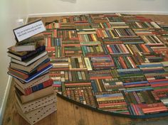 Book rug: Artist Pamela Paulsurd has crafted a rug made out of recycled book spines. (via Recyclart)