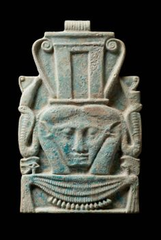 Amulets of the head of the fertility goddess Hathor were popular items in both Egyptian and Nubian burials. This elaborate openwork amulet of blue glazed faience takes the form of a plaque. On the front, the goddess appears frontally, with her characteristic cow's ears and horns. Her headdress incorporates a shrine, similar to those seen on Hathor-headed sistra. She is flanked by a pair of uraeii, one in the red crown of Lower Egypt and the other in the white crown of Upper Egypt. NUBIAN