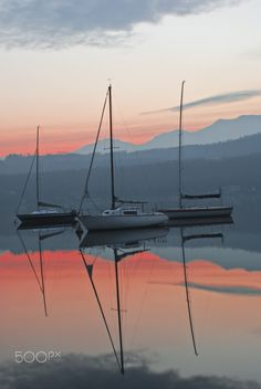 Boats at sunset - boats reflected on the water of the lake, in the light of sunset