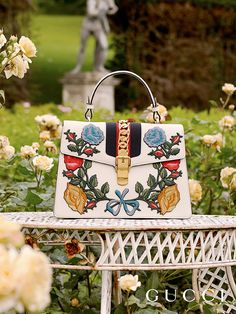 Wreathed with embroidered floral appliqués, the Gucci Sylvie top handle bag from Gucci Cruise 2017.