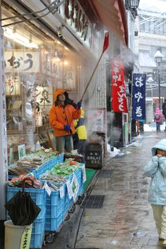 Nozawa Onsen, Japan  Clearing snow from the awnings