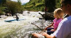 Spectators watch a kayaker shoot the rapids on Gore Creek - near Vail, CO