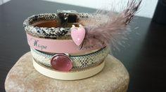 """Armband in beige/gebroken en roze leer met tekst """"LOVE, PEACE & HOPE"""" met leerschuivers en veertje en magneetsluiting.  € 25,="""
