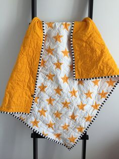 Ready for immediate shipping, this whole cloth quilt was created using fabric designed exclusively for Little Colley Design, and is the perfect addition to any nursery. MEASUREMENTS Measuring 33 inches by 40 inches (approximately), this quilt has been washed and dried prior to shipping so future washing should not cause further shrinkage.  COLORS The front fabric is a white background with bright golden orange stars. The backing fabric is a subtle crosshatch pattern in bright golden orange…