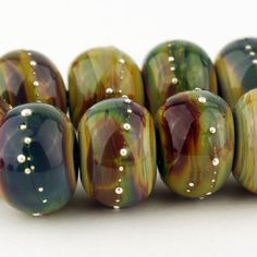 This set of 10 handmade lampwork glass beads is made with classic raku glass and accented with fine silver wire.  Measures: 10 x 13mm