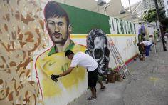 Grafiteiro trabalha em um mural em comemoração da Copa do Mundo no Rio de Janeiro