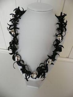 Handgemaakte rubbere ketting.Het rubber is zwart en daartussen zitten 5 grote zilveren kralen.De ketting is sterk en licht.Lengte 65 cm.