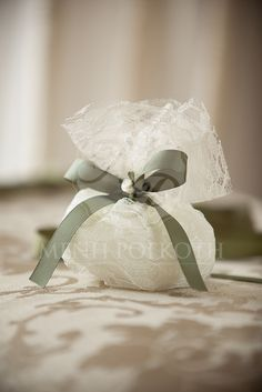 Elegant lace pouch on ivory colour with olive grosgrain bow and satin flower. The pouch holds 7 sugared almonds koufeta.