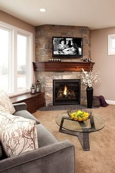 Corner fireplace with warm cherry wood mantel. Love the stone, love the mantle love the TV above