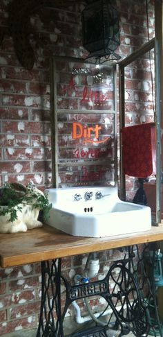 Vintage sink on an old singer seeing machine base with an old window behind it, then hooked up to the hose for an outdoor sink!! I love it!!  Just have to highlight the red lettering with some white paint!