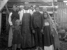 Mustavalkoinen valokuva, jonka keskellä poseeraa pitkään hameeseen puettu nainen ympärillään runsaasti lapsia.Kuva: A. R. Niemi (1911)