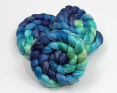 4.0 oz of hand painted merino wool/ bamboo fiber/ tussah silk top (roving) spinning fiber. This roving is painted in shades of blue and green.