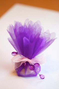 but with white tulle and purple bow --- Purple tulle favour with a pink ribbon and purple jewel.  From www.elenamaria.co.uk