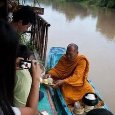 Give ..food to the monk ..by boat...^^