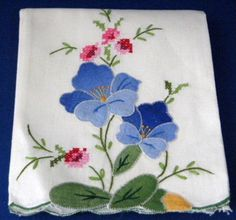 This is a hand towel or guest towel made of white cotton with a hand embroidered cross stitch, satin stitch and hand appliqued flowers and leaves design. The towel measures 22 inches high by 14 inches